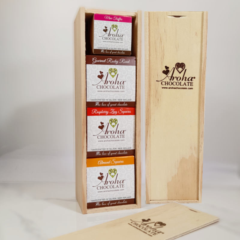 Aroha Tower. A wooden box containing a box of Almond Squares, Raspberry zing squares, large gourmet rocky road and a box of mini truffles